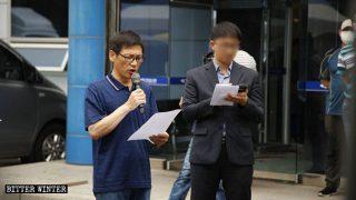 Acompañado por su abogado, un miembro de la IDT lee su declaración.