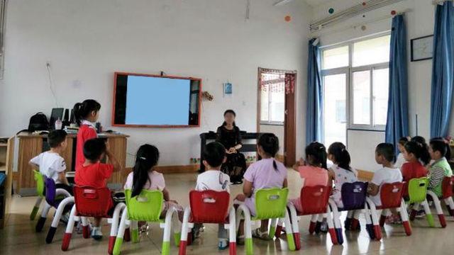 Una maestra de kínder habla con los niños en una clase.
